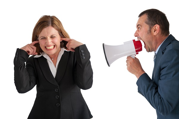 businesswoman being yelled at by male manager businessman through a loudhailer or megaphone isolated on white